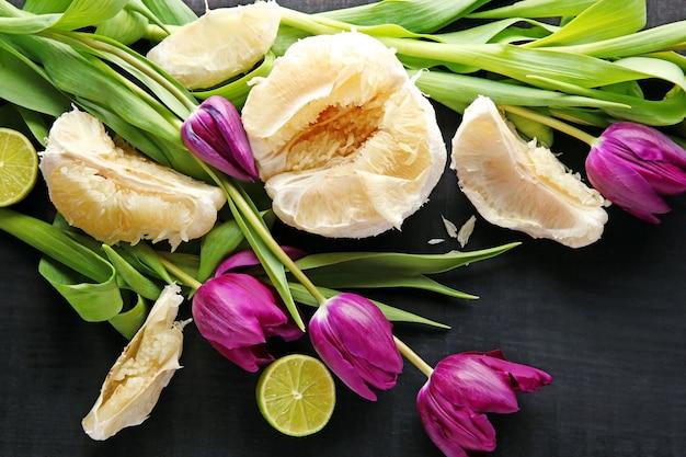 Verse violette tulpen en citrusvruchten op zwarte achtergrond, bovenaanzicht