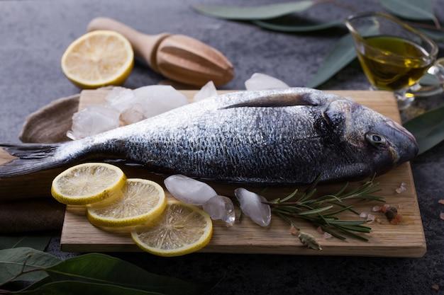 Verse vis dorado. ruwe doradovissen en ingrediënt voor het koken. verse zeug-hoofdbrasem dorade met zout, kruiden en peper.