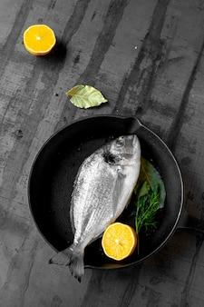 Verse vis en zwarte koekenpan op donkere zwarte achtergrond. vis met kruiden en groenten. koken achtergrond concept