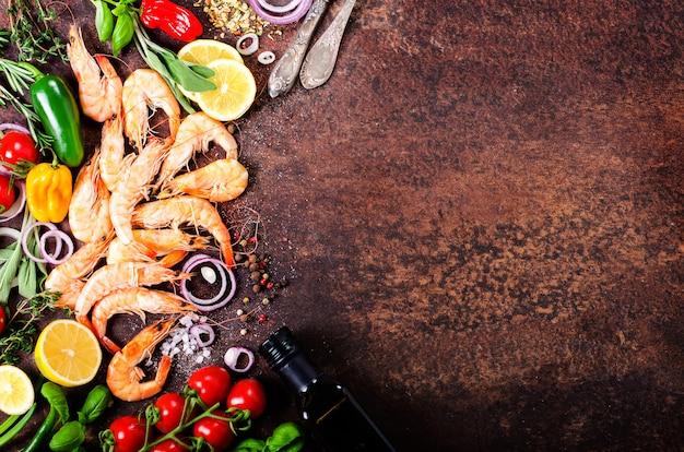 Verse vis, garnalen met kruiden, specerijen en groenten op donkere vintage achtergrond. gezond eten, dieet of koken concept.