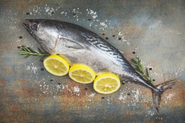 Verse vis met kruiden specerijen rozemarijn en citroen - rauwe vis zeevruchten op zwarte plaat achtergrond bovenaanzicht, longtail tonijn, oost-kleine tonijn vis