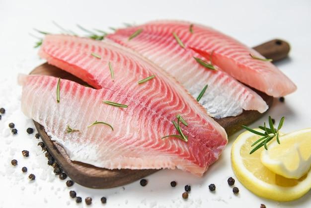 Verse visfilet gesneden voor biefstuk of salade met kruiden specerijen rozemarijn en citroen - rauwe tilapia filet vis en zout op witte stenen achtergrond en ingrediënten voor het koken van voedsel