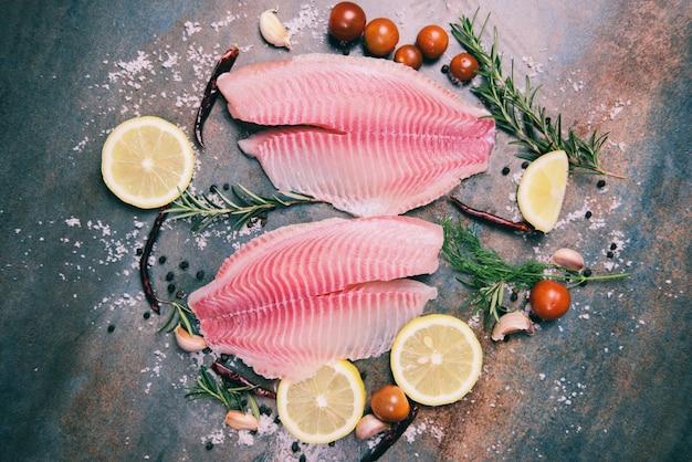 Verse visfilet gesneden voor biefstuk of salade met kruiden specerijen rozemarijn tomaat en citroen - rauwe tilapia filet vis en zout op donkere stenen achtergrond en ingrediënten voor het koken van voedsel