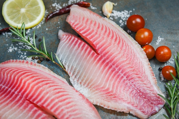 Verse visfilet gesneden voor biefstuk of salade met kruiden specerijen rozemarijn tomaat en citroen - rauwe tilapia filet vis op plaat en ingrediënten voor het koken van voedsel