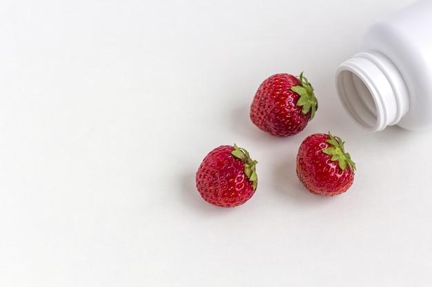 Verse vitamines als aardbeien uit de fles met witte pillen.