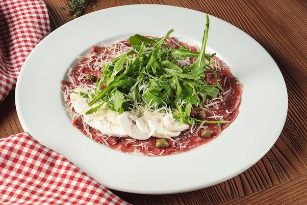 Verse vitello tonnato (schotel van koude, gesneden kalfsvlees) met rucola en parmezaanse champignons op witte plaat.