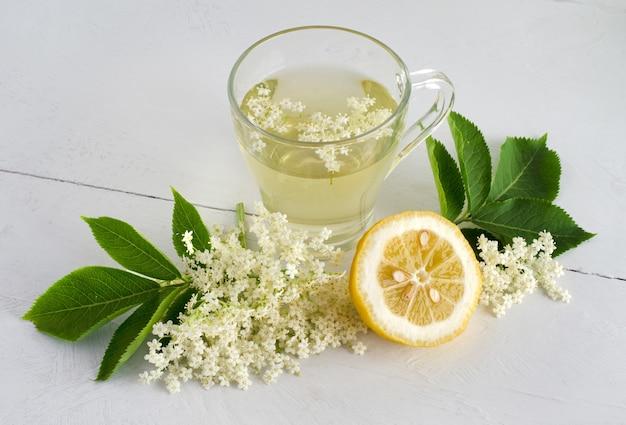 Verse vlierbessenbloemdrank met gesneden citroen op witte tafel. bovenaanzicht.