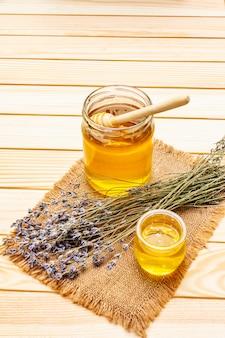 Verse vloeibare honing in glazen potten met een houten honingdipper