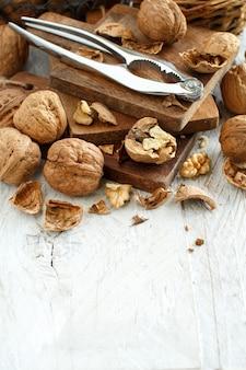 Verse walnoten met een notenkraker op een oude houten tafel