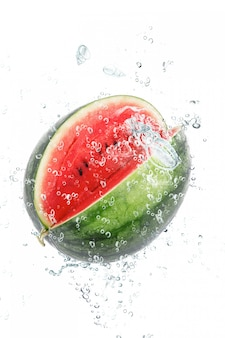 Verse watermeloen die in water valt