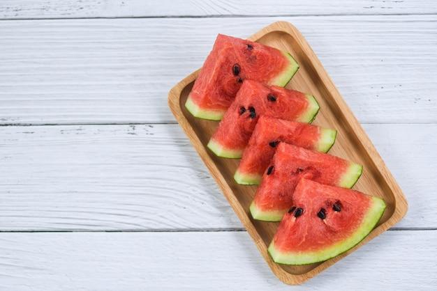 Verse watermeloen die op wit hout wordt gesneden