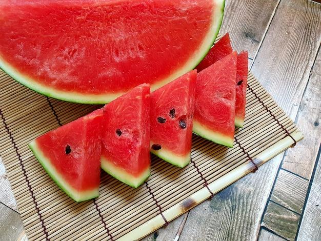 Verse watermeloenplak op een bamboemat en een houten achtergrond