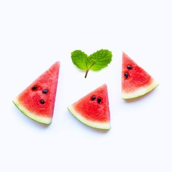 Verse watermeloenplakken met muntbladeren op wit.