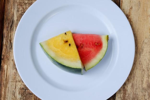 Verse watermeloenplakken op witte plaat op houten achtergrond