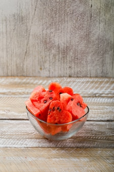 Verse watermeloenstukken in een glaskom op houten en grunge achtergrond