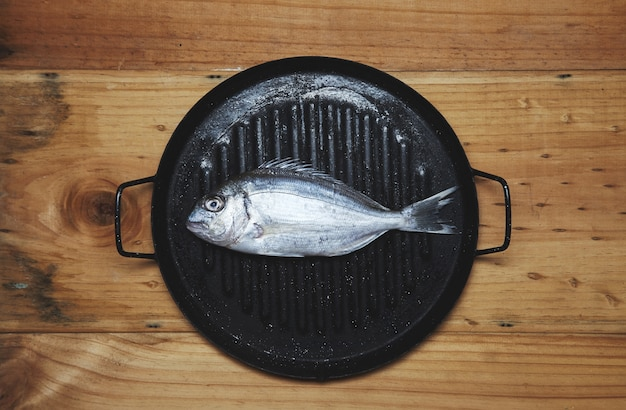 Verse wilde zeebrasem op grillpan klaar om te koken