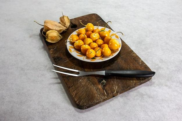 Verse winterkersen physalis kaapse kruisbes aguaymanto uvilla op een bord en naast een vork