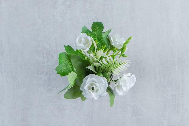 Verse witte bloemen in een houten kruik, op de witte tafel.
