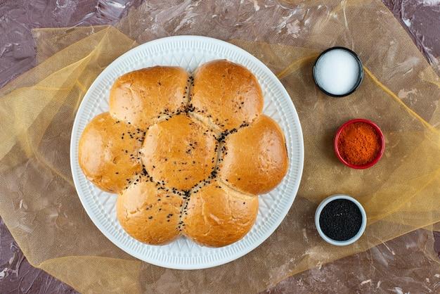 Verse witte broodjes met zout en peper op een lichte achtergrond.