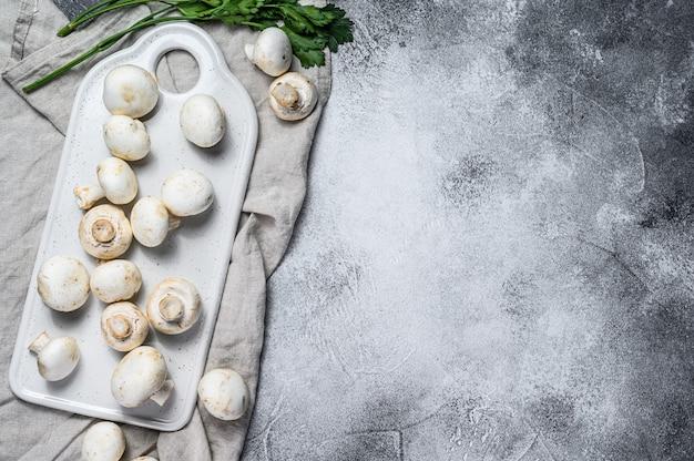 Verse witte champignon op hakbord. grijze achtergrond. bovenaanzicht ruimte voor tekst