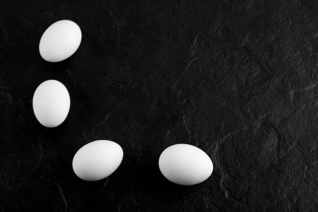 Verse witte eieren op zwarte ondergrond