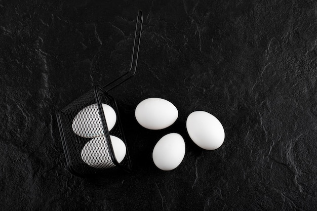 Verse witte eieren uit zwarte container.