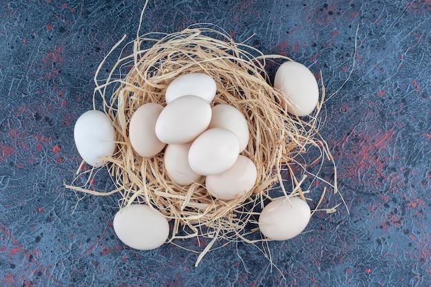 Verse witte en bruine kippeneieren met hooi.