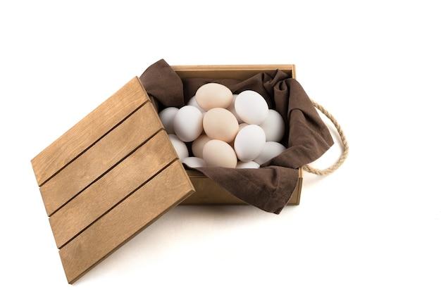 Verse witte en bruine kippeneieren worden in een houten verpakking met deksel geplaatst.