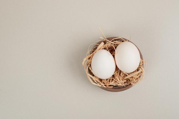 Verse witte kippeneieren met hooi in houten kom.