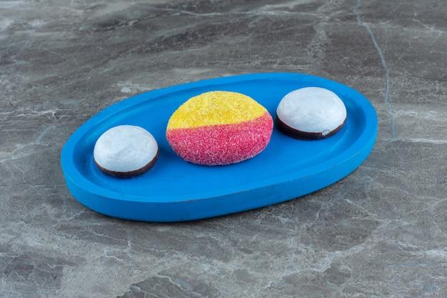 Verse witte koekjes met oeach-vormkoekje op blauw houten bord.