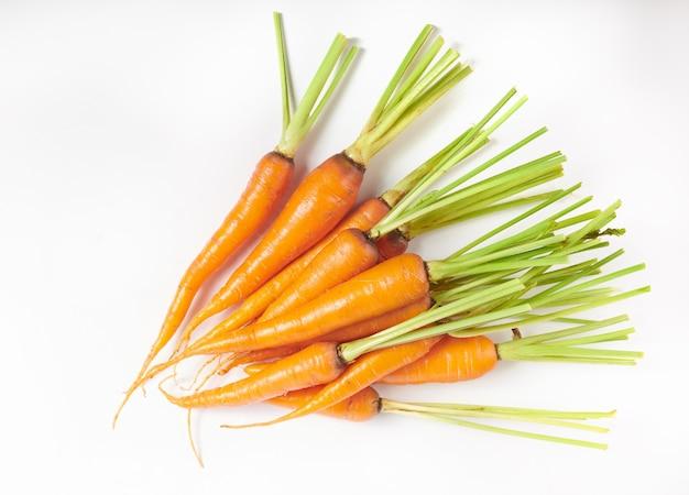 Verse wortel die op wit oppervlak als element van het pakketontwerp wordt geïsoleerd. bovenaanzicht. plat leggen. vers uit de biologische tuin van thuisgroei. voedsel concept.