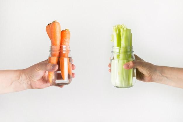 Verse wortel en selderij in metselaarkruik met water. bespaar de zomeroogst. storage. zero waste.