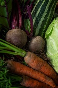 Verse wortelen, bieten, courgette en kool in een mand. nieuwe oogst seizoensgroenten. vitaminen en gezondheid uit de natuur. detailopname. verticaal.