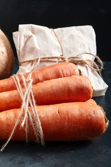 Verse wortelen, donkere achtergrond. voedselbezorgingsconcept, milieuvriendelijke verpakking. kopieer de ruimte, close-up.