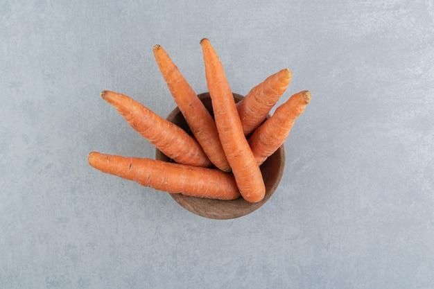 Verse wortelen in de kom, op het marmer.