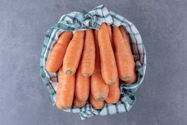 Verse wortelen op handdoek in de kom, op het marmeren oppervlak.
