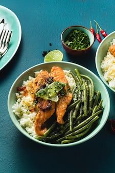 Verse zalm gebakken met gember en knoflook in kokosmelk, met basmatirijst en sperziebonen in platen op tafel. gezond recept voor het hele gezin.
