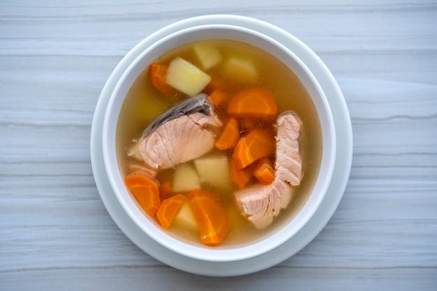 Verse zalm vissoep met wortelen, aardappelen en uien in een witte plaat