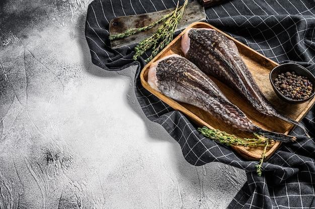 Verse zeeduivel zonder kop op een houten dienblad met een hakmes