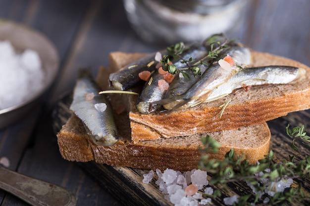 Verse zeevis koud water kleine vis zoals spiering, sardine, ansjovis op een eenvoudige achtergrond met verse spinazie, schijfjes citroen, peulvruchten voor het concept van de juiste gezonde natuurlijke voeding. bovenaanzicht