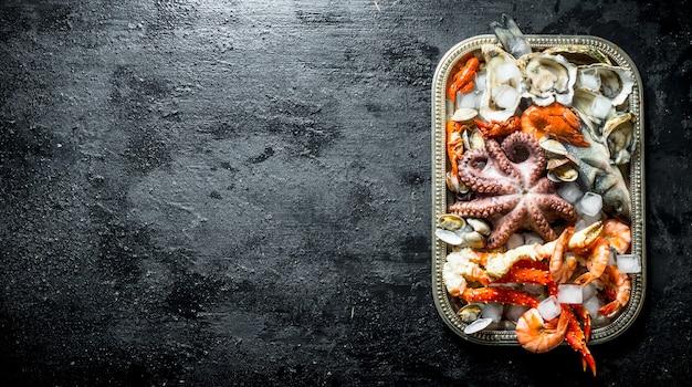 Verse zeevruchten op een dienblad met stukjes ijs. op zwarte rustieke achtergrond
