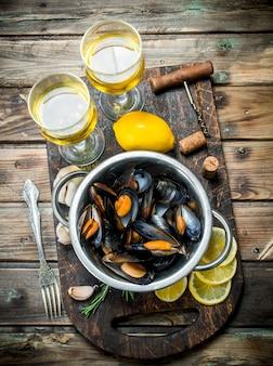 Verse zeevruchten tweekleppige schelpdieren in een pot witte wijn op een rustieke tafel.