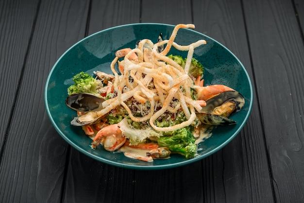 Verse zeevruchtensalade met garnalen, mosselen en groenten op een zwarte