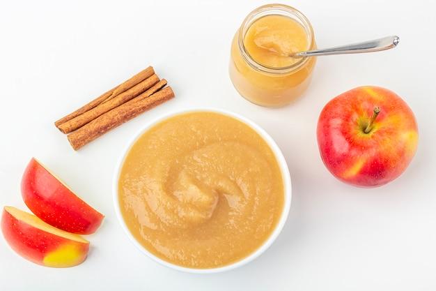 Verse zelfgemaakte appelmoes in witte kom en pot met fruitpuree op witte tafel. het concept van goede voeding en gezond eten. biologisch en vegetarisch eten. babyvoedsel. ruimte voor tekst kopiëren