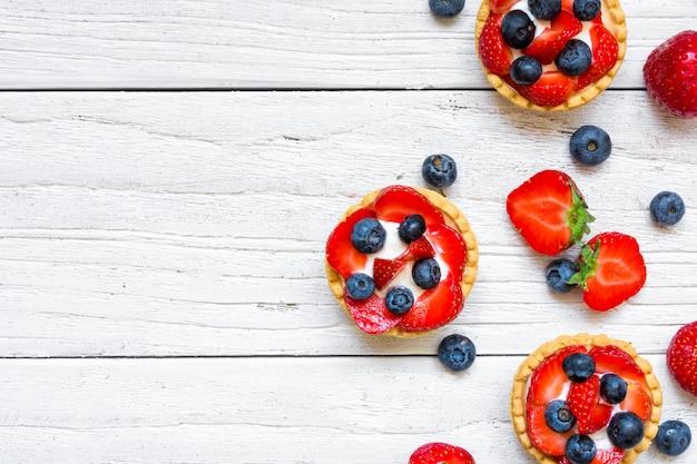 Verse zelfgemaakte bessen taarten met aardbeien en bosbessen met verse bessen