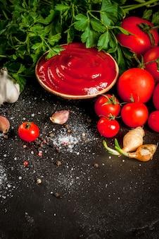 Verse zelfgemaakte biologische tomatensaus of ketchup in een kleine kom met de ingrediënten - peterselie uien knoflook tomaten zout peper op een zwarte stenen betonnen tafel verticaal boven