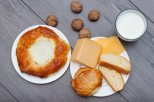 Verse zelfgemaakte broodjes met sesam en kaas op houten achtergrond met glas melk, appel, noten.