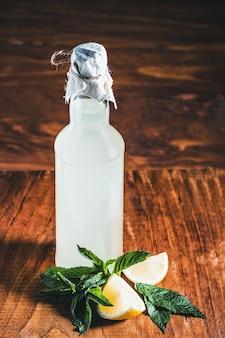 Verse zelfgemaakte fles limonade, citroenen en munt op een houten achtergrond.
