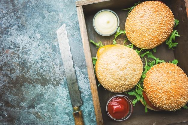 Verse zelfgemaakte hamburger in een doos met pikante saus en kruiden op donkere stenen achtergrond. bovenaanzicht met kopieerruimte