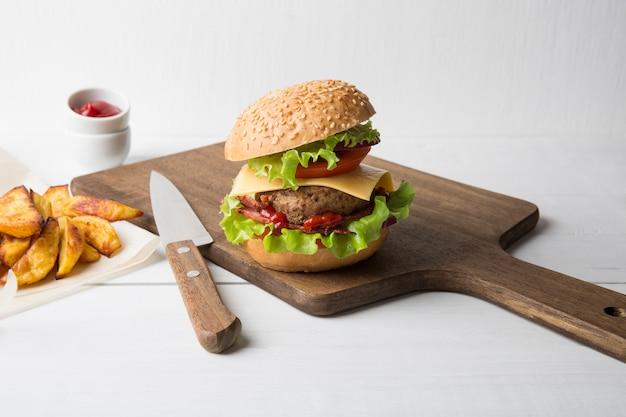 Verse zelfgemaakte hamburger met vlees, ketchup en frietjes op een lichte houten achtergrond. kopieer ruimte.